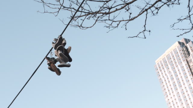 vídeos de stock, filmes e b-roll de sneakers hanging on a power line - arame