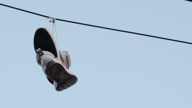 vídeos de stock, filmes e b-roll de sneakers hanging on a telephone line - arame