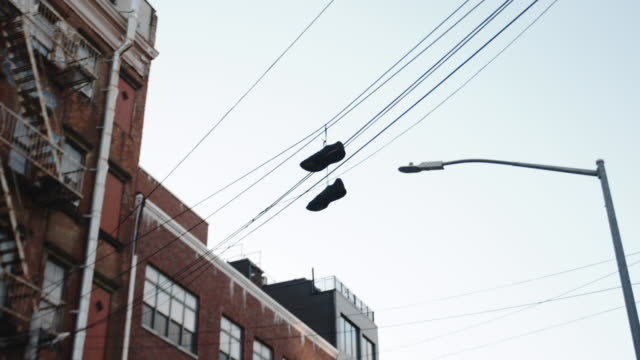 sneakers hanging on a telephone wire - scarpe da ginnastica video stock e b–roll