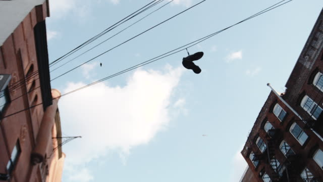 sneakers hanging on a telephone wire - telephone line stock videos and b-roll footage