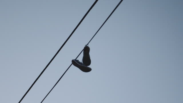 sneakers hanging over a telephone line at sunrise - telephone line stock videos and b-roll footage