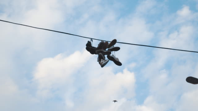 sneakers hanging over a telephone line - linea telefonica video stock e b–roll