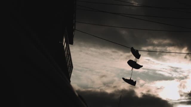 sneakers hanging over an electric line during the summer of 2017. - telephone line stock videos and b-roll footage