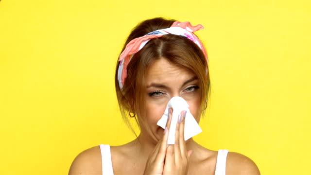 4k sneezing sick woman - yellow background - sneezing stock videos & royalty-free footage