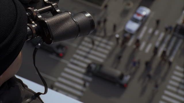 stockvideo's en b-roll-footage met a sniper viewing a funeral procession from the top of a building. - geheime dienstagent