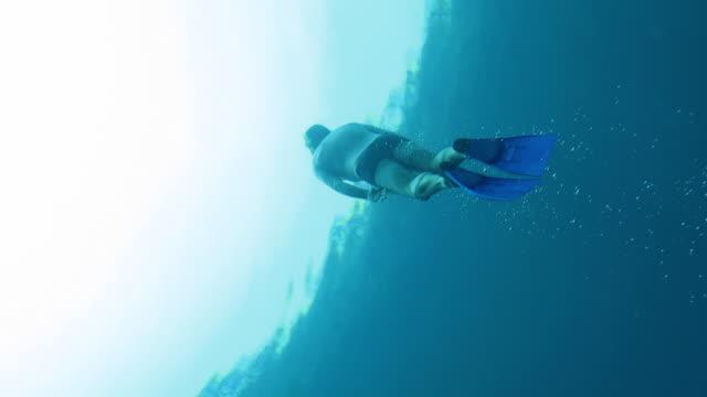 stockvideo's en b-roll-footage met snorkel diver diving to the sufaces. - zwemvlies