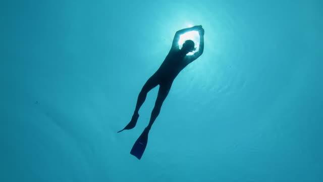 stockvideo's en b-roll-footage met snorkel diver floating backlit by the sun - zwemvlies