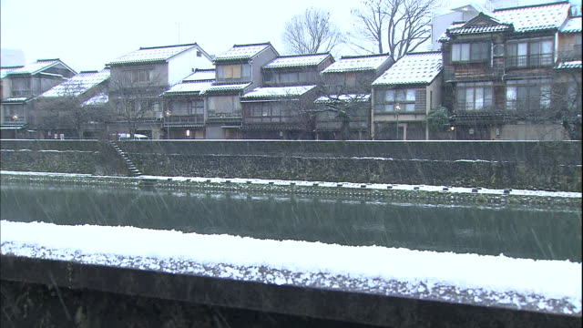 snow accumulates on river banks and on the roofs of traditional wooden houses in the kazue-machi chaya district. - ishikawa prefecture stock videos and b-roll footage