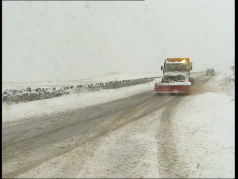 snow across the country; england ext/snow gv 'road closed' sign on snowy road pull out as bv car drives slowly along gv snow plough along road... - road closed englisches verkehrsschild stock-videos und b-roll-filmmaterial