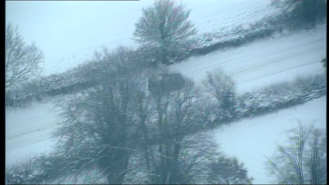 aerials of newbury and swindon air views / aerials car driving slowly along icy country road tractor and trailer along on farm houses sign for lady... - トラクター点の映像素材/bロール