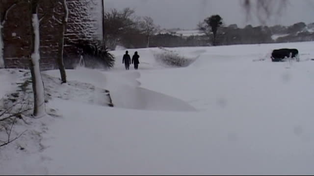 Snow and blizzards cause disruption across south of England CHANNEL ISLANDS Jersey Deep snowdrift Man away from car covered by snow