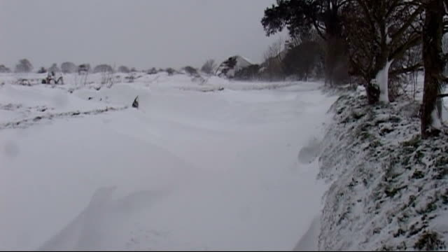 Snow and blizzards cause disruption across south of England Jersey CHANNEL ISLANDS Jersey EXT Man walking along snow covered road past car buried in...