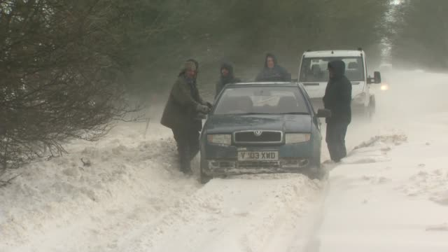 Snow and freezing conditions still causing havoc across UK ENGLAND Car stuck in snow drift in country road Tractor moving snow in country road