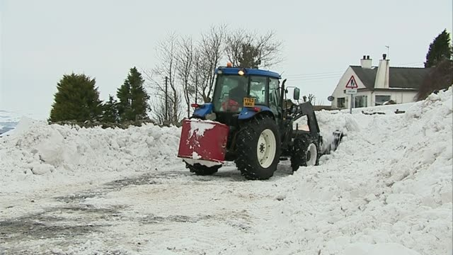 Snow and freezing conditions still causing havoc across UK SCOTLAND Snowplough tractor clearing snow from country road Woman walks along though deep...