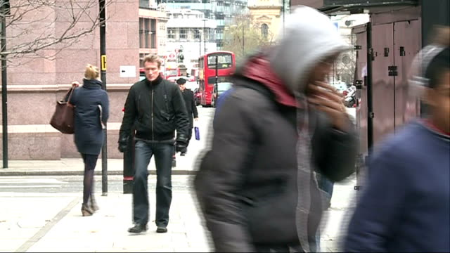 vídeos de stock e filmes b-roll de snow and freezing temperatures across britain; england: london: ext various shots people along in cold and windy weather around chancery lane tube... - cold temperature