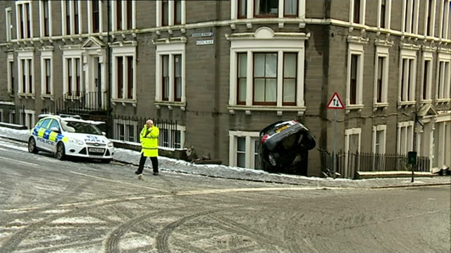 snow and high winds forecast for uk; dundee: police officer and police car at scene of car crash with car down embankment through railings in front... - スコットランド ダンディー点の映像素材/bロール
