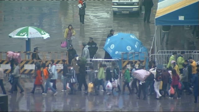 snow and ice strand thousands at railway stations snow scenes china guangzhou ext security forces lining barricades set up outside railway station to... - control点の映像素材/bロール