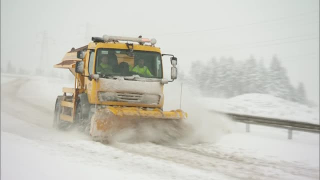 vídeos de stock, filmes e b-roll de snow and sleet cause disruption in parts of the uk england cumbria truck along road clearing snow van along road with snow - chuva congelada