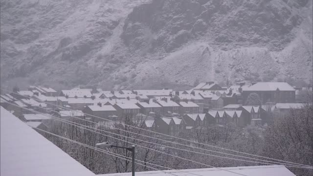 vídeos de stock, filmes e b-roll de snow and sleet cause disruption in parts of the uk wales gwynedd blaenau ffestiniog various shots of roofs of houses with snow and hillside people... - chuva congelada