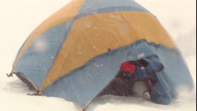 snow and wind whip past a tent where campers remove their gear. - tenda video stock e b–roll