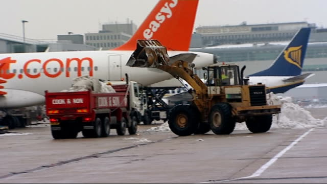 sussex gatwick airport truck with load of snow and tractor on runway / easyjet plane / tractor tipping snow into back of truck / easyjet and ryanair... - snow vehicle stock videos and b-roll footage