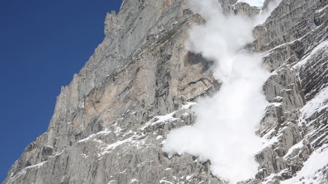 snow avalanche thunders down steep mountain face - avalanche stock videos and b-roll footage