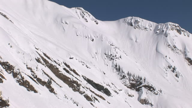 snow blankets rugged mountain slopes. - hill stock videos & royalty-free footage