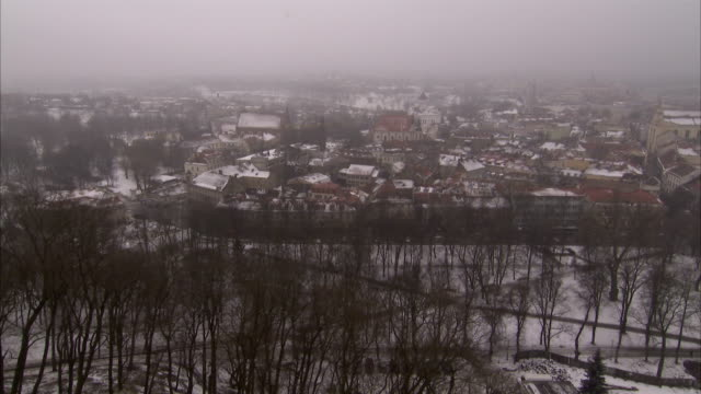 Snow blankets the city of Siauliai on a foggy day. Available in HD.
