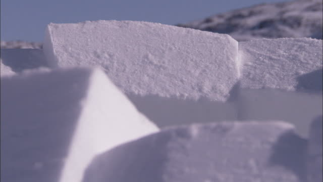 snow blocks form a half-built igloo. available in hd. - igloo stock videos & royalty-free footage