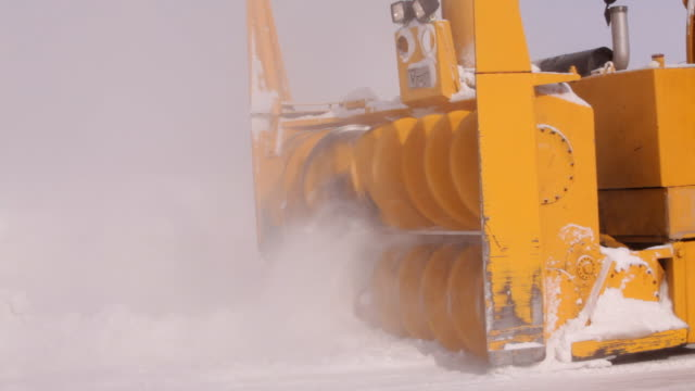 A snow blower working and passing