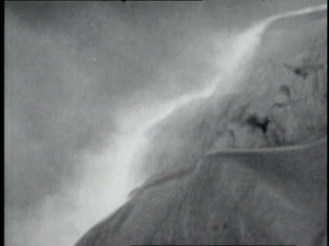 vidéos et rushes de snow blowing off top of mountain / hikers suiting up with gear and helmets in blowing snow - 1952