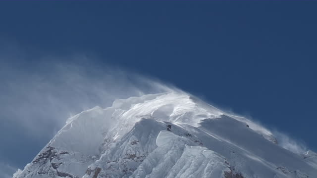stockvideo's en b-roll-footage met ms snow blowing with wind on snow covered peak of mount everest with blue sky / mt. everest, nepal - mount everest