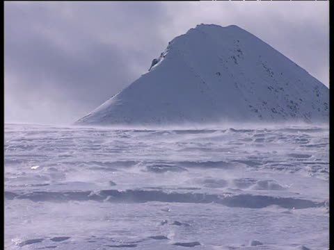 Snow blows across icy surface snow covered mountain in background Svalbard