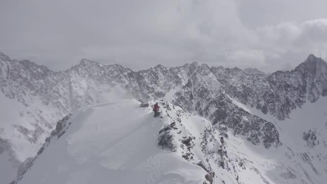 vídeos de stock, filmes e b-roll de neve sopra na cara de um alpinista andando em uma montanha coberta de neve e gelo nos alpes na áustria - cordilheira
