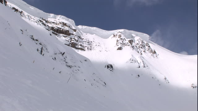 vidéos et rushes de snow blows off a drift at the top of a snowy mountain. - neige fraîche