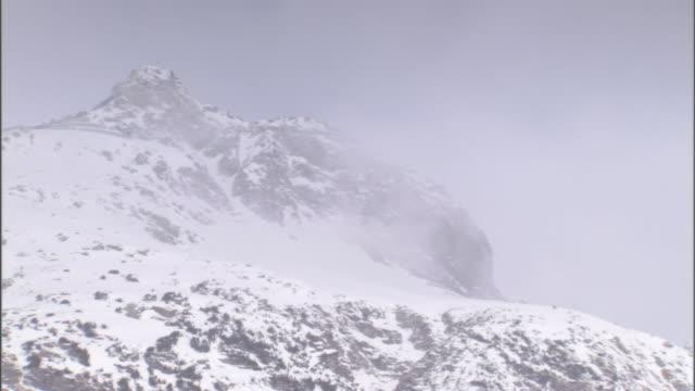 vídeos de stock e filmes b-roll de snow blows on a mountain peak. - nevão