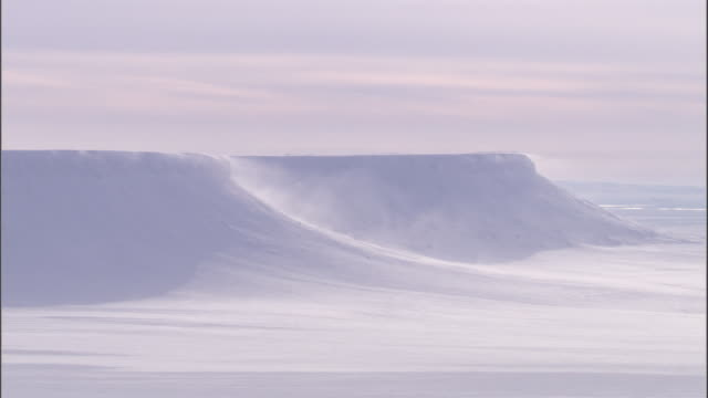 Snow blows over the top of an icy plateau on Svalbard, Norway.
