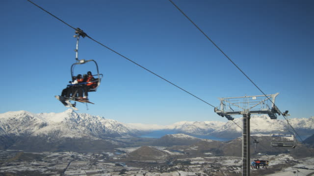 ws snow boarders and skiers riding ski lift over coronet peak / queenstown, new zealand - queenstown stock videos & royalty-free footage