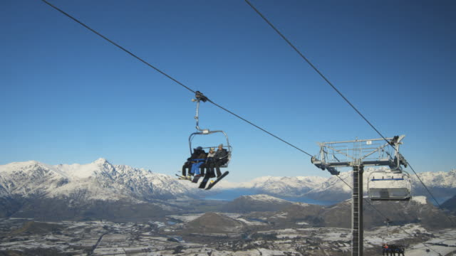 WS T/L Snow boarders and skiers riding ski lift over Coronet Peak / Queenstown, New Zealand