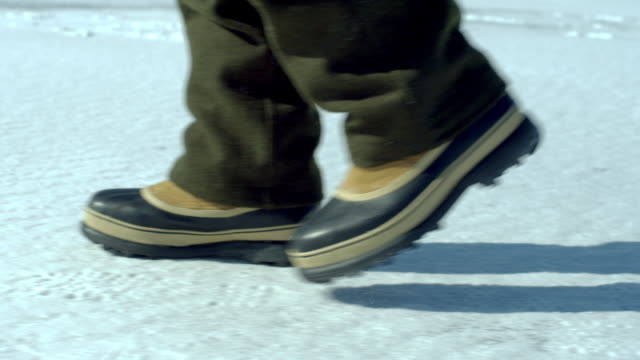 snow boots walk across a snow covered ground. - newoutdoors stock videos & royalty-free footage