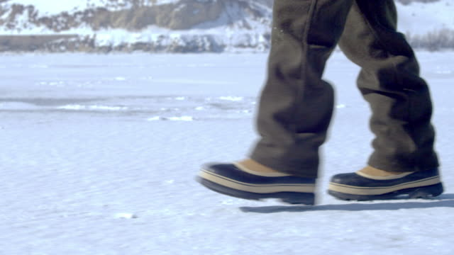 snow boots walking across the snowy ground. - one teenage boy only stock videos and b-roll footage