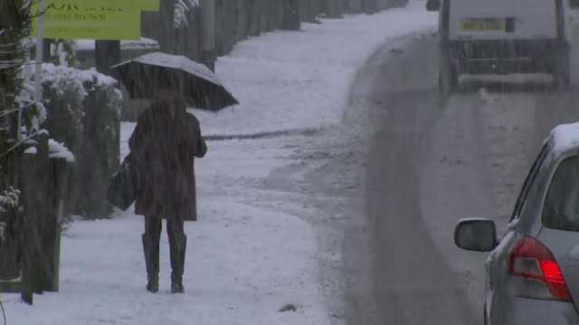 snow brings chaos across the north of england england greater manchester stockport man along street as snow falls people and traffic along street - stockport bildbanksvideor och videomaterial från bakom kulisserna