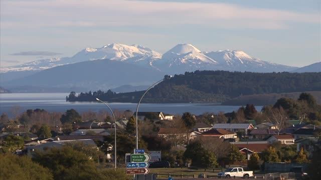 snow capped mount ngauruhoe and mount ruapehu seen across water of lake taupo - ngauruhoe stock videos & royalty-free footage