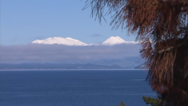 snow capped mount ngauruhoe and mount ruapehu seen from above shore of lake taupo - ngauruhoe stock videos & royalty-free footage