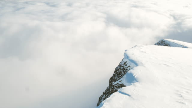 Snow capped mountain above clouds in Wengen