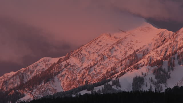 Snow capped mountain glows red in dawn light.
