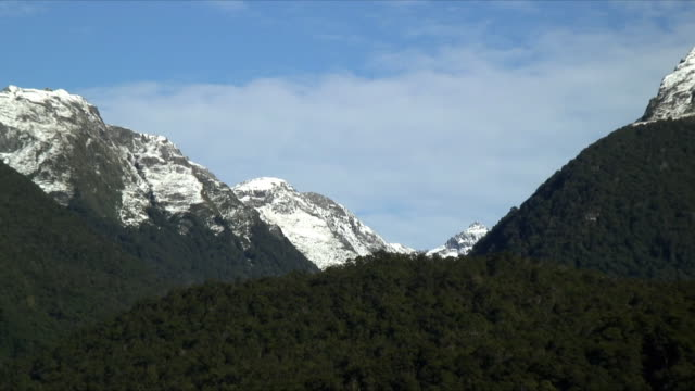 ws zo snow capped mountain peaks and rural highway in foreground, mt aspiring national park, new zealand - new zealand stock-videos und b-roll-filmmaterial