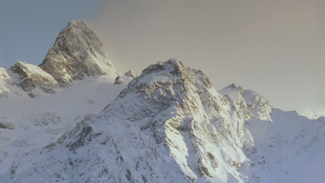 stockvideo's en b-roll-footage met cu snow capped mountain peaks lit by the sun - stilstaande camera