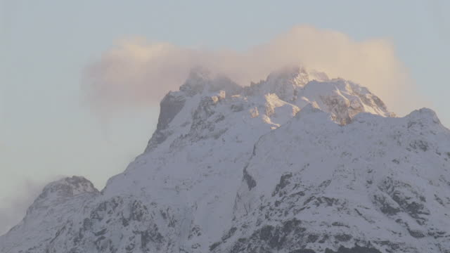 stockvideo's en b-roll-footage met ms snow capped mountain peaks under a partly cloudy sky - stilstaande camera