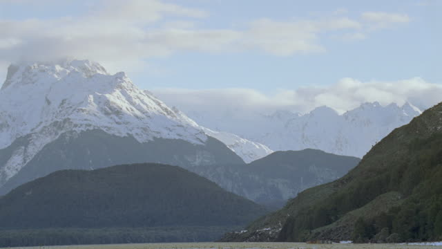 stockvideo's en b-roll-footage met ws snow capped mountain peaks under a partly cloudy sky - stilstaande camera